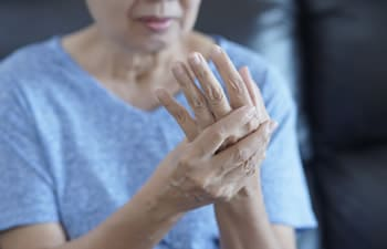 A woman holding her aching wrist